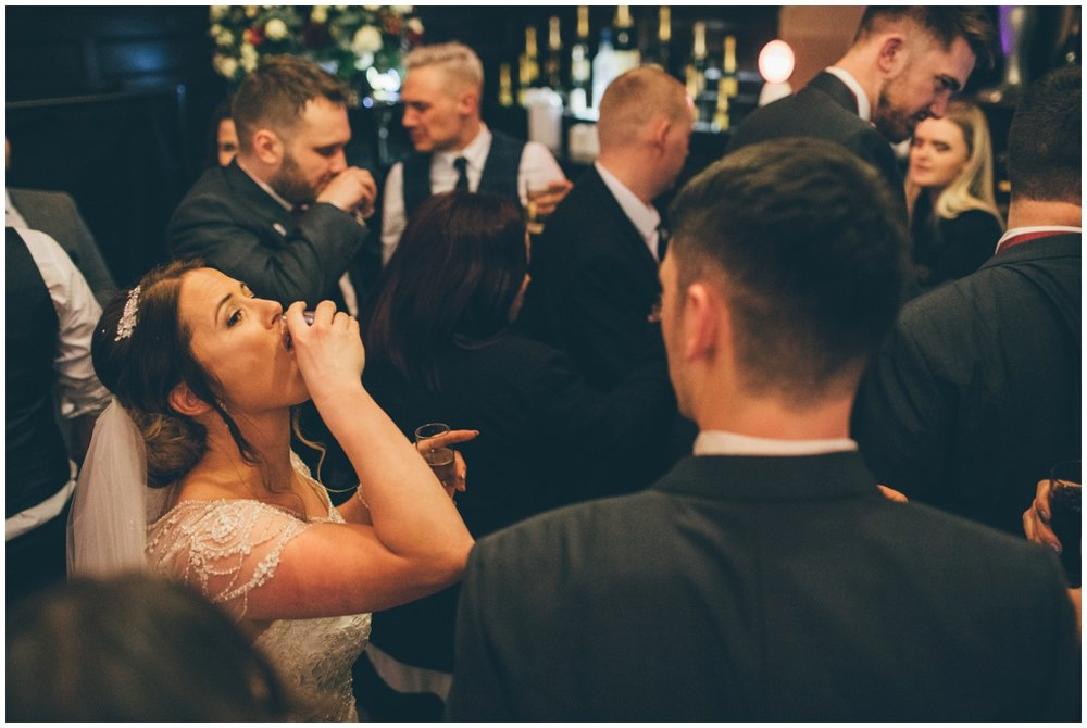 Bride does a shot during her wedding celebrations at Peckforton Castle.