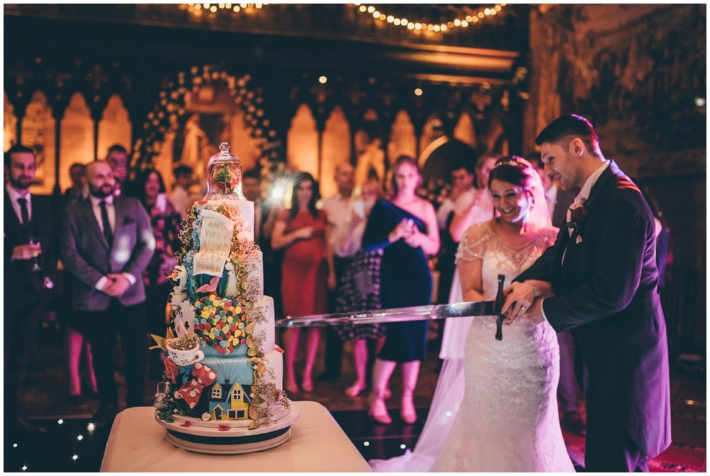 The newlyweds cut their amazing disney-themed wedding cake at Peckforton Castle.