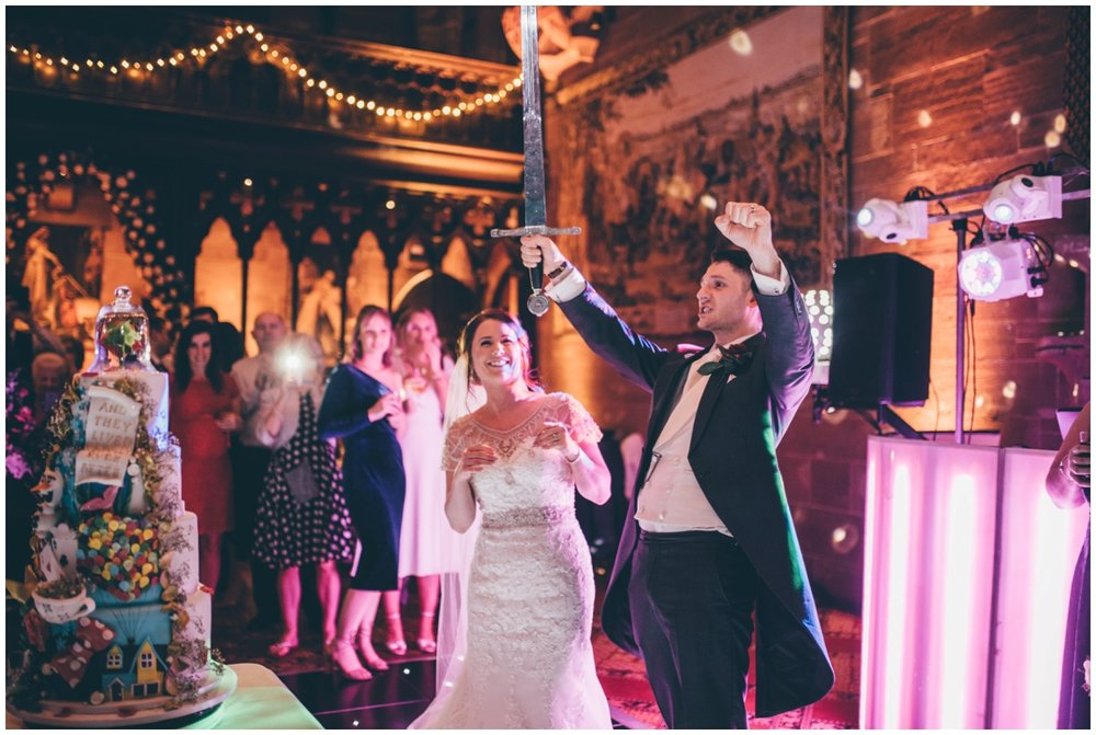 Groom celebrates cutting his amazing wedding cake at Peckforton Castle.