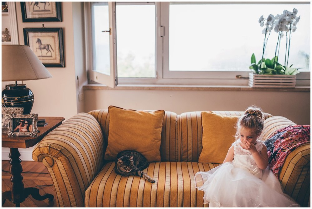 Adorable flower girl sits with the family cat, waiting for the bridal party to get ready.