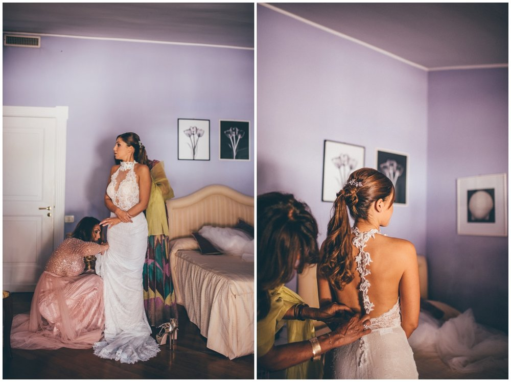Everyone helps the bride get into her beautiful wedding gown.