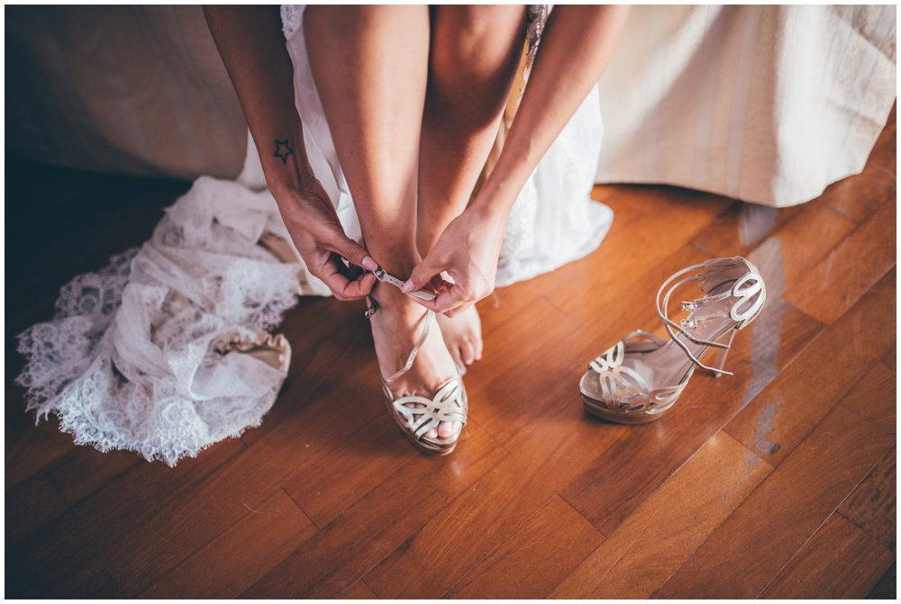 Beautiful bride puts on her high heeled wedding shoes.