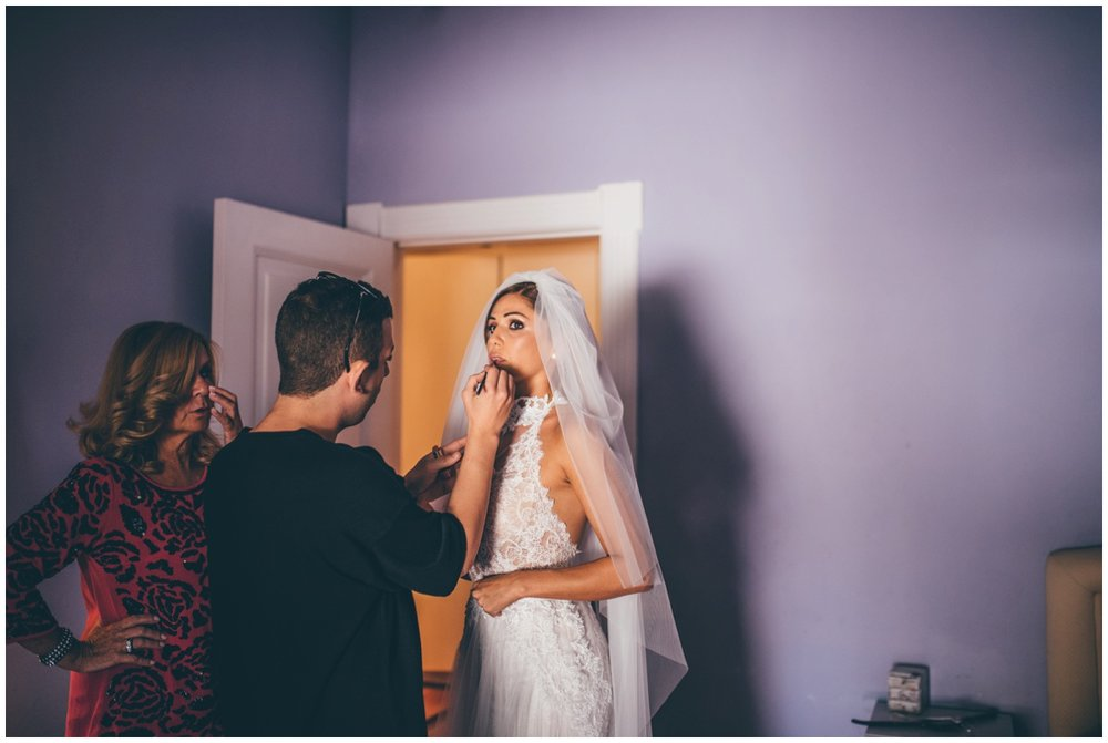 The MUA applies the last of the beautiful Italian bride's lipstick.
