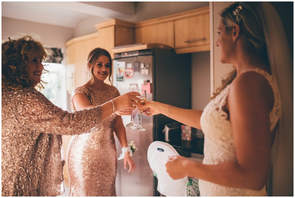 Bride and her bridesmaids cheers a champagne on the wedding morning.