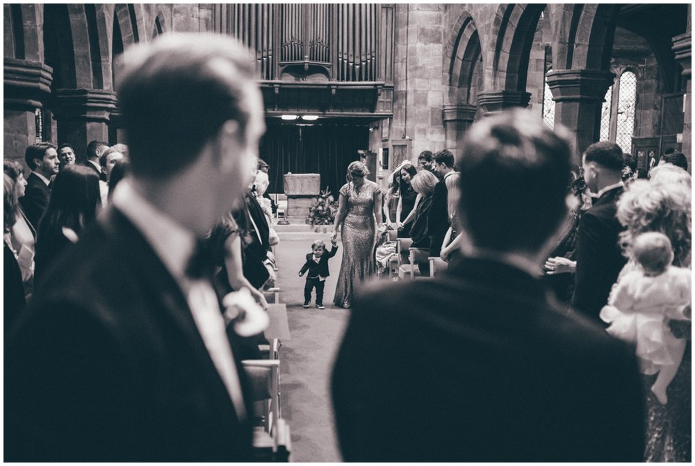 Page boy walks down the aisle in Knutsford Church.