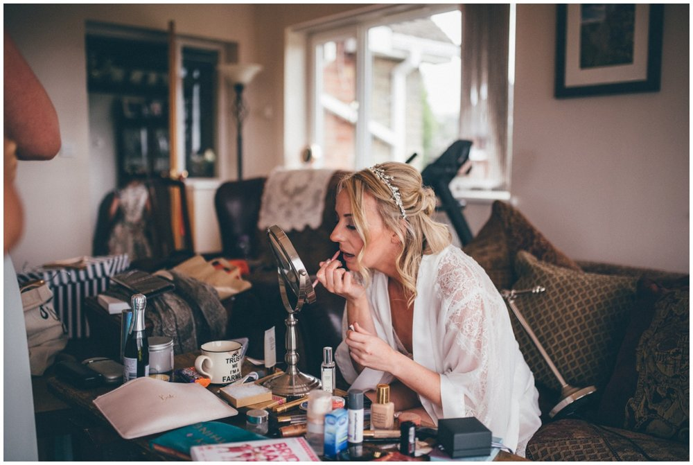 Bride puts on her own make-up on the morning of her own wedding in Staffordshire.