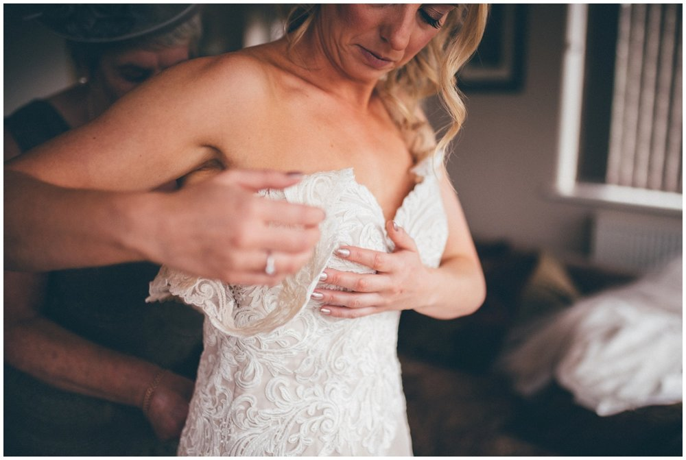 Beautiful bride puts her lace wedding gown on.
