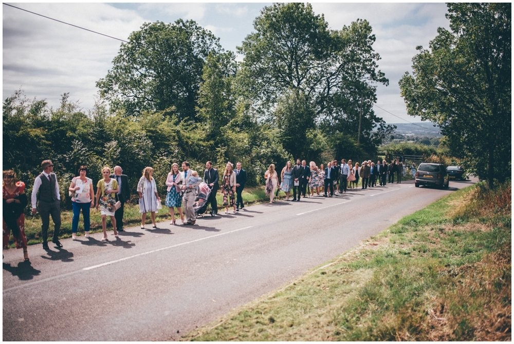 Wedding guests walk up the pretty country road, shot by Cheshire wedding photographer.
