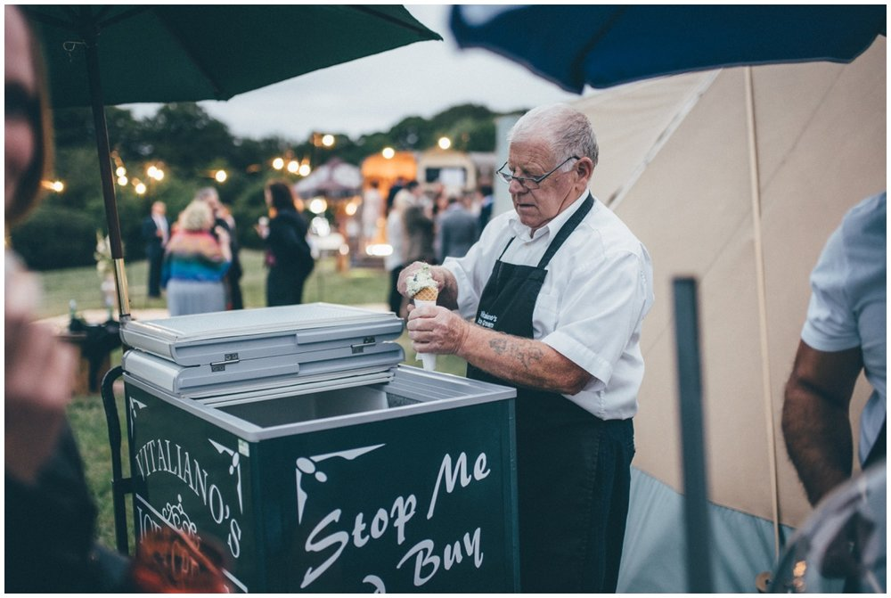 Ice cream man scoops ice cream at a tipi wedding.