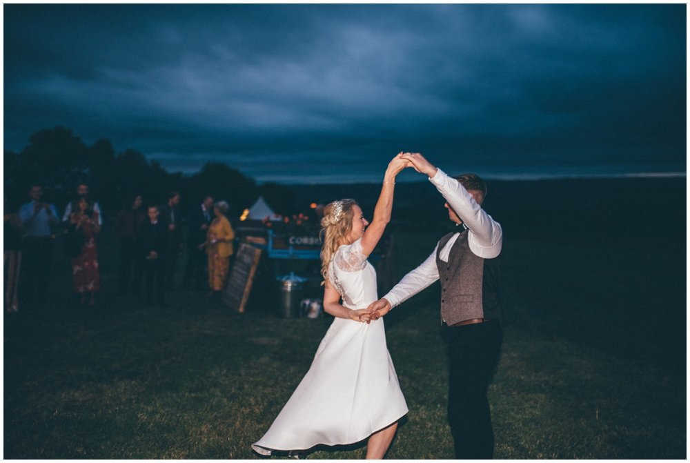 Bride and groom have their First Dance outside their wedding tipi in Staffordshire.