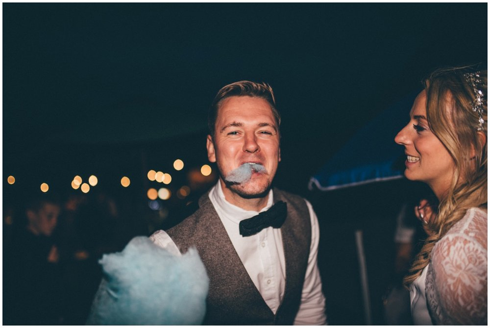 Bride and groom share candy floss at their tipi wedding in Staffordshire.
