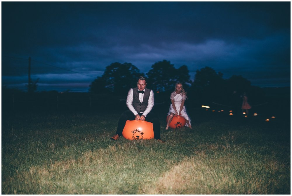 Bride and groom play on space hoppers during their tipi wedding reception in Staffordshire.