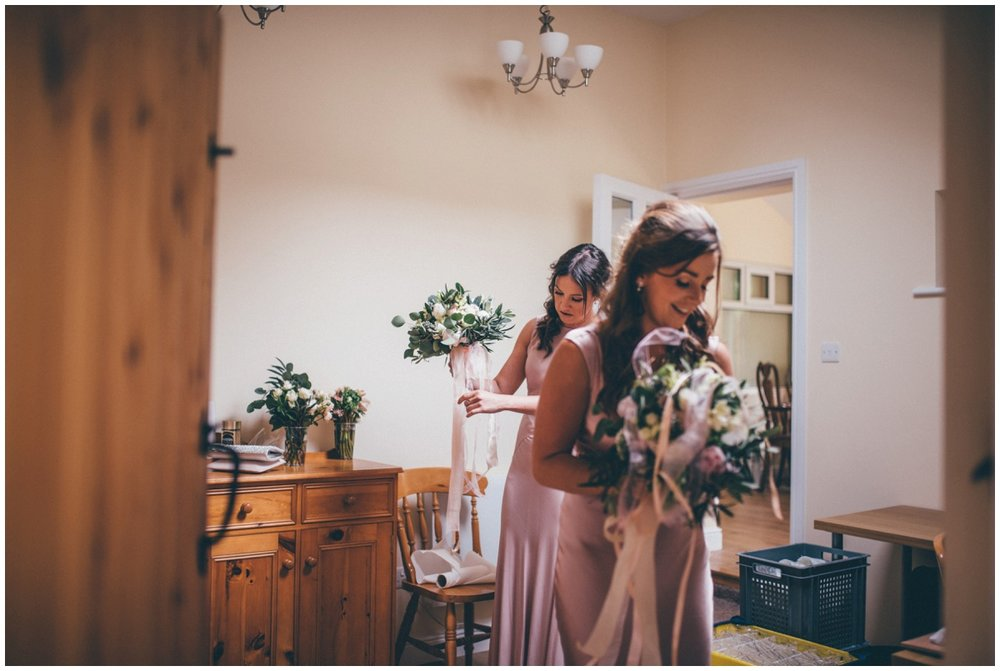 The bridesmaids in their pink dresses collect their Red Floral wedding bouquets.