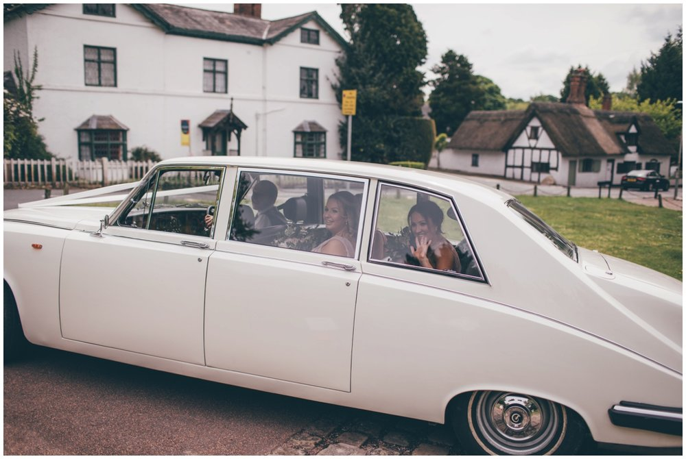 Bridesmaids arrive at St Mary's church in a vintage old wedding car for spring time wedding.