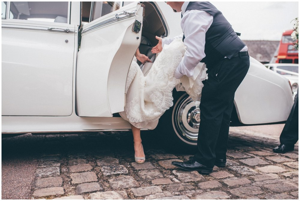 Bride steps out of her vintage wedding car in her Jimmy Choo shoes.