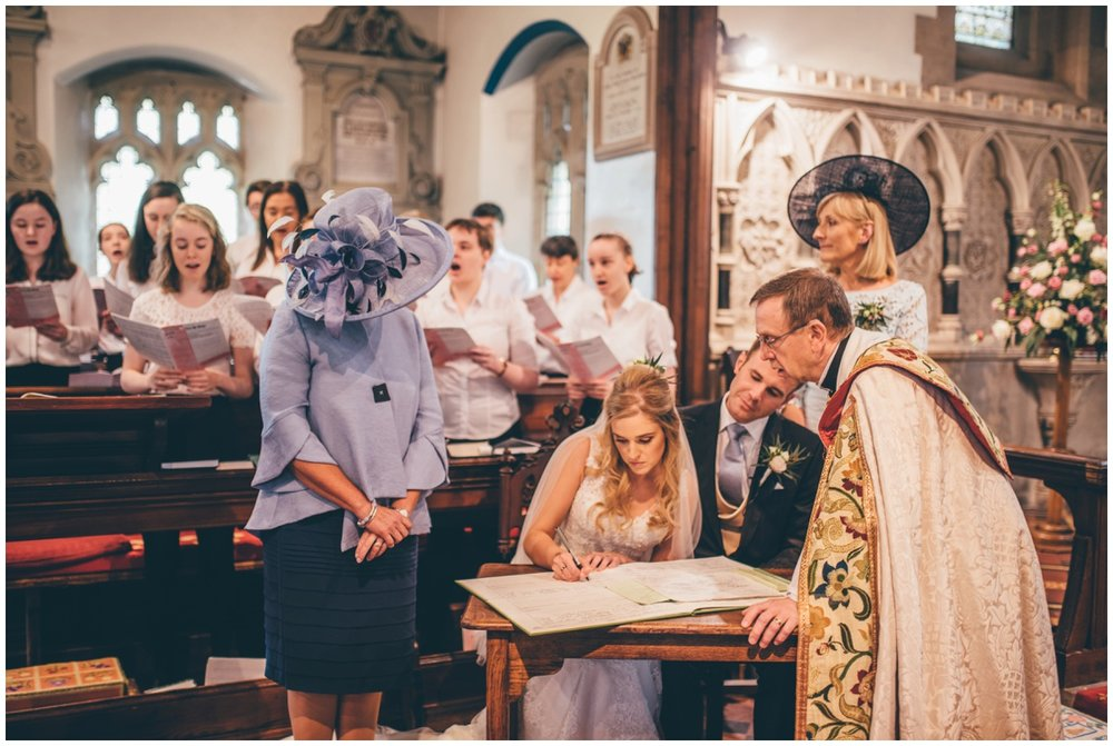 Bride and groom sign the register after their Wedding ceremony in St Mary's Church in Cheshire.