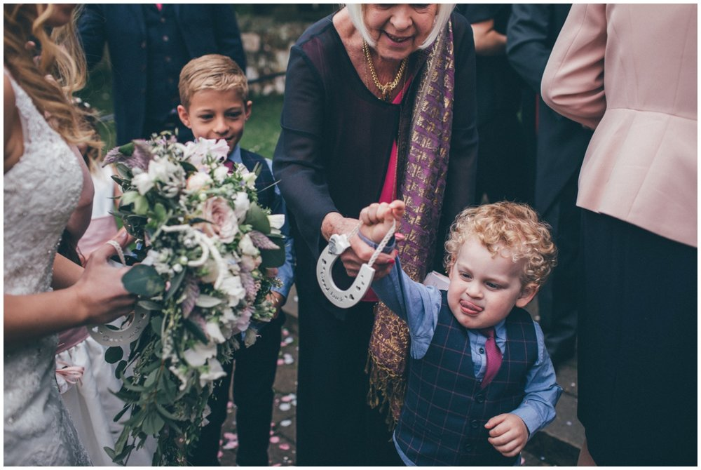 Cute little wedding guest gives a horseshoe to the bride.