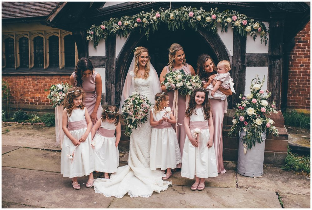 The bride and her bridesmaids pose for wedding photographs outside St Mary's Church in Cheshire.