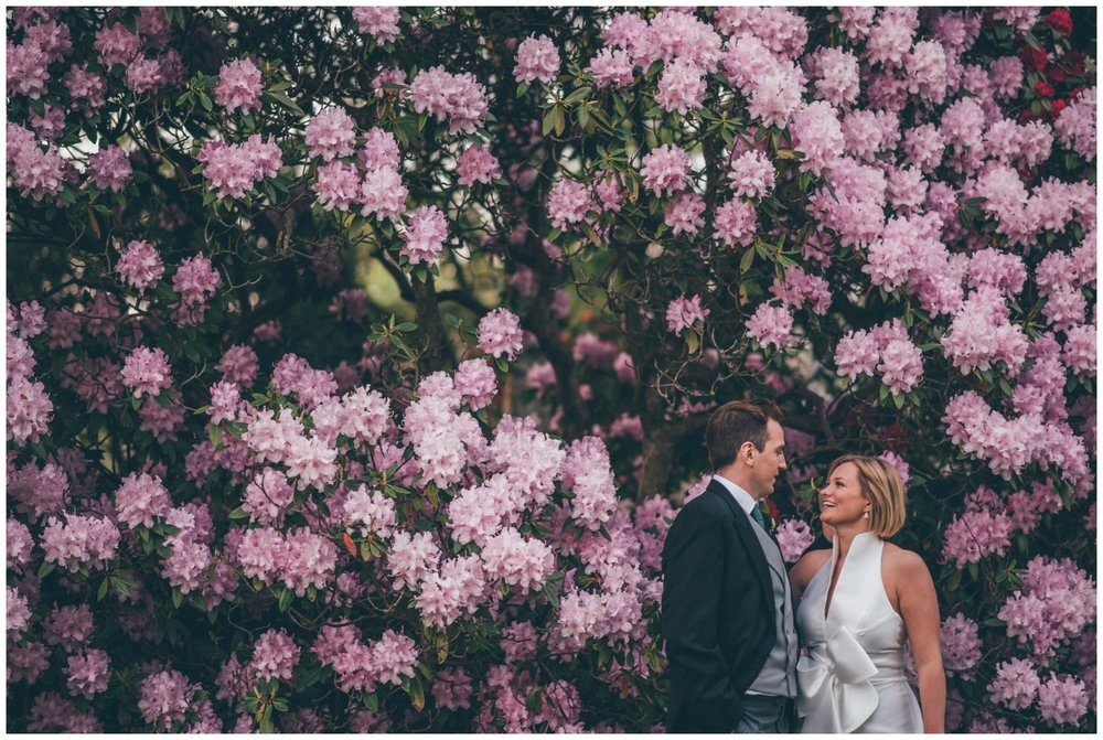 Bride and groom have their wedding photographs taken in front of stunning wall of flowers at Rudding Park Hotel in Yorkshire.