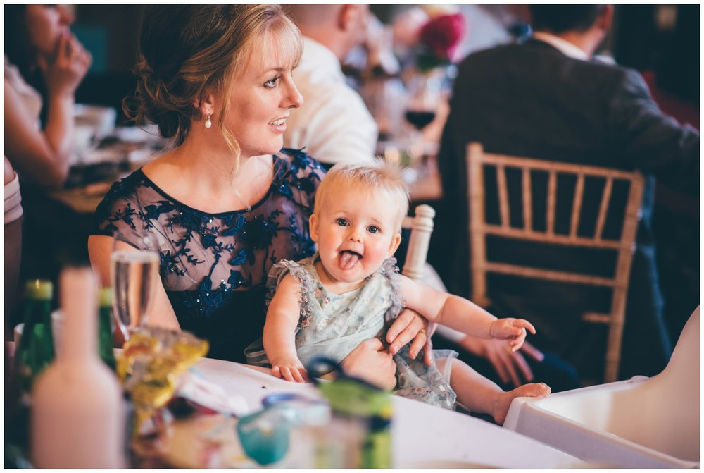 Cute little wedding guest enjoys cake during the wedding speeches.