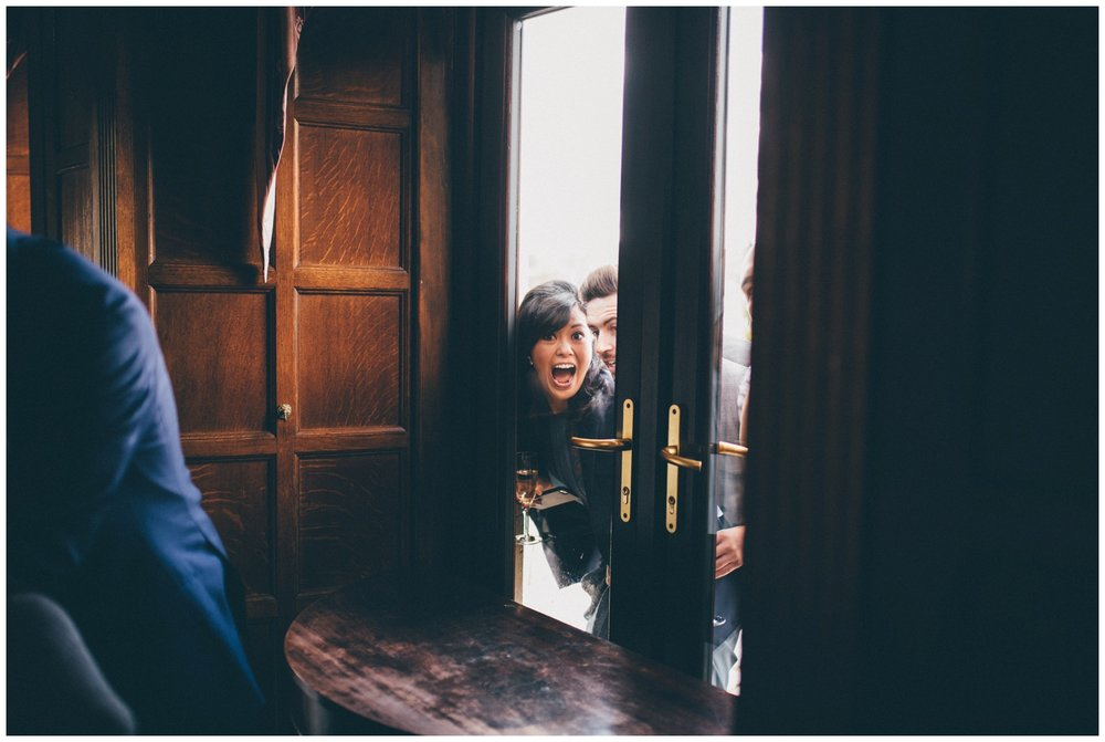 Family members make wedding guests laugh through the window at Langdale Chase hotel in the Lake District.