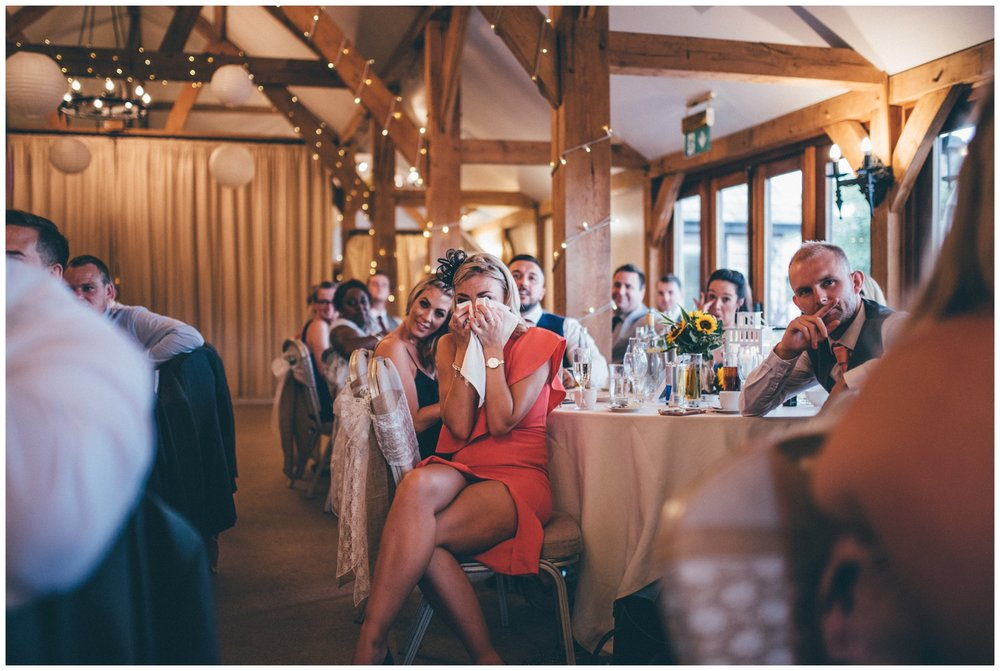 Female wedding guest cries into a napkin during the speeches at Sandhole Oak Barn in Cheshire.