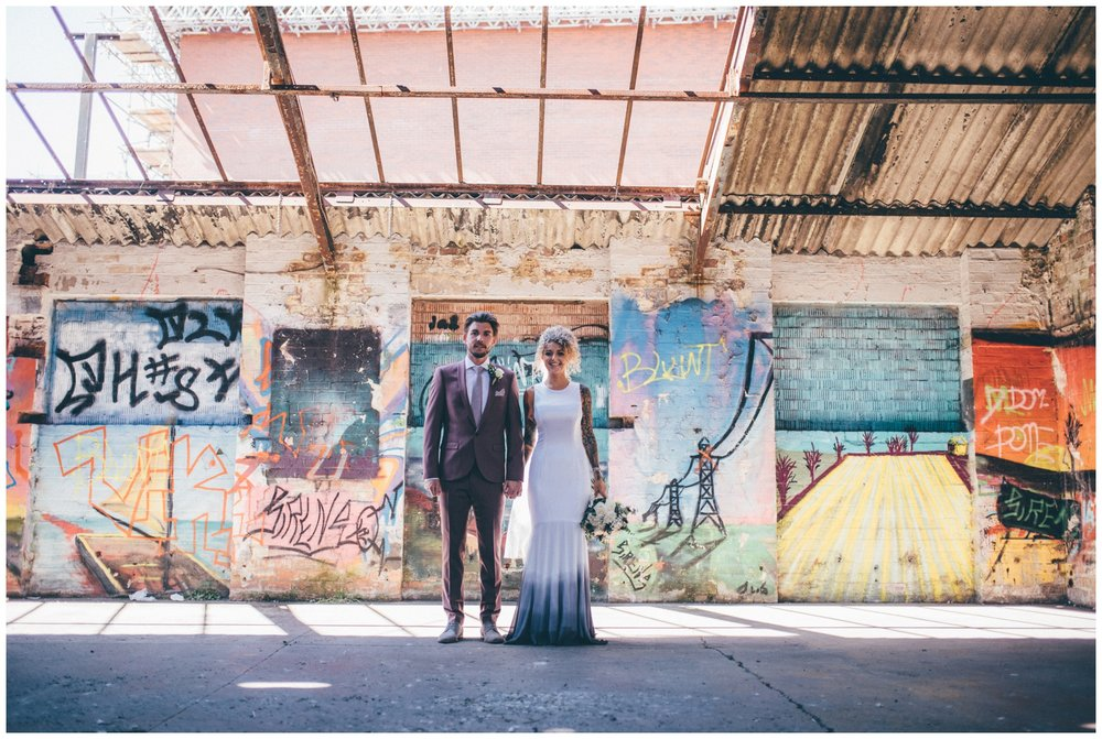 Cool tattooed bride and groom pose or their wedding photographs in graffiti filled car park in Chester city centre.