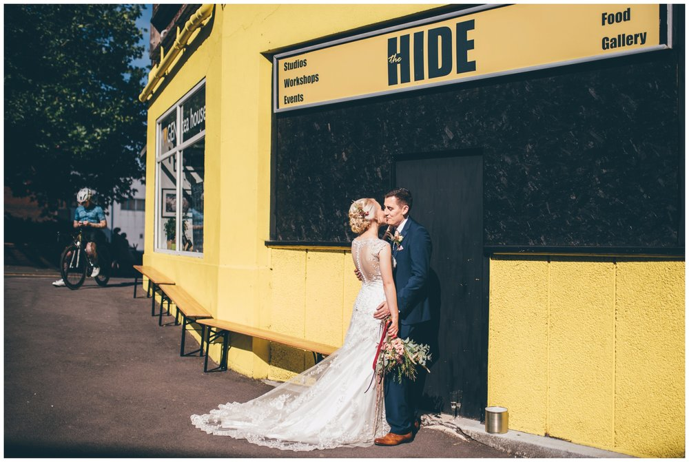 Bride and groom share a kiss outside their colourful city centre wedding venue, The Hide in Sheffield.