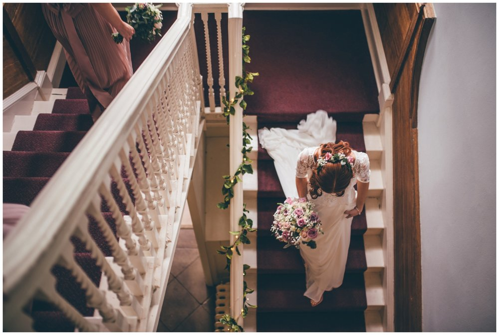 Bride walks down the stairs of Cheshire wedding venue, Trafford Hall, on the way to her wedding ceremony.