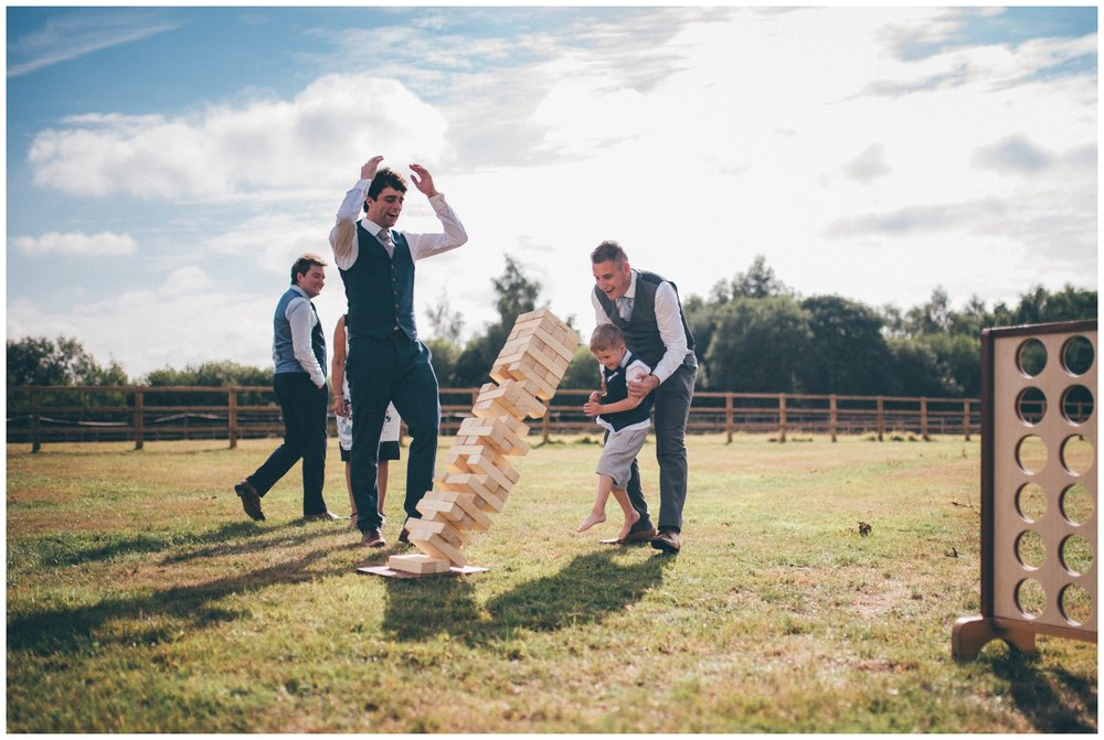 The jenga falls at over in summer lawn games at Holford Estate wedding in Cheshire.