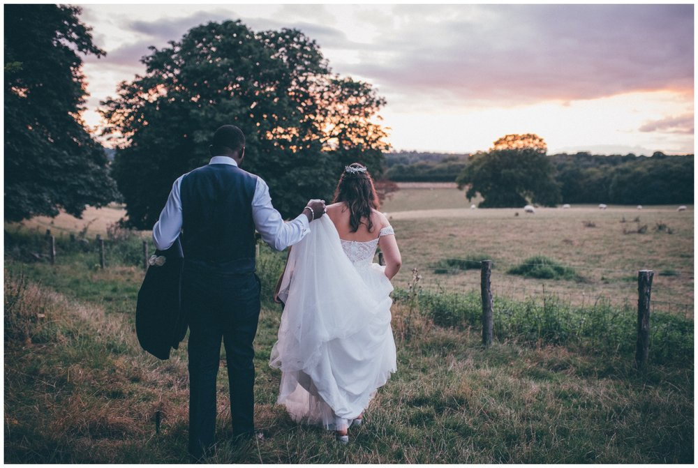 Bride and groom walk off together int the sunset at Gaynes Park, wedding venue near London.
