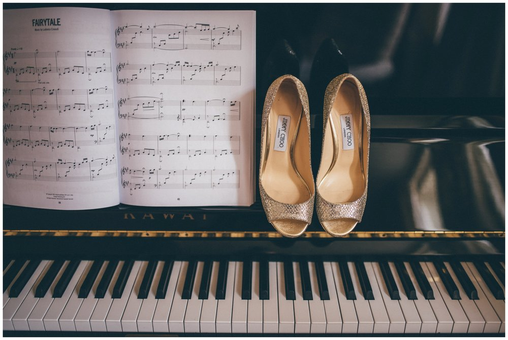 Gold and sparkly Jimmy Choo wedding shoes against a backdrop of a grand piano ahead of a Cheshire wedding at Merrydale Manor.