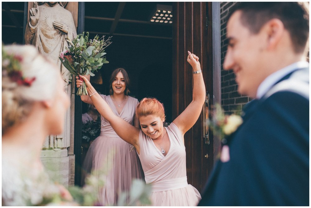 Bridesmaid celebrates the newlyweds at she walks out of church cheering after the wedding in Sheffield.
