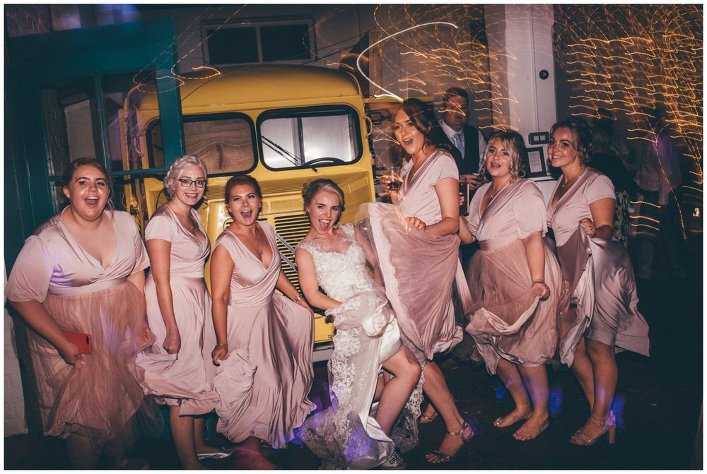 Bride and her bridesmaids all dance in their dusky pink dresses, in front of the for truck at The Hide wedding in Sheffield.