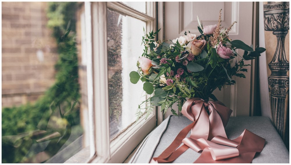 The most beautiful pastel and dusky pink wedding bouquet held together bye ribbons, in the window at Swinton Park Estate in Yorkshire.