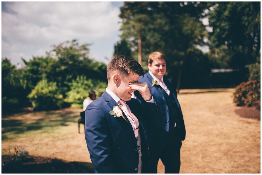 Groom cries as he watches his bride walk down the aisle at their outdoor wedding ceremony at Tilstone House in Cheshire.