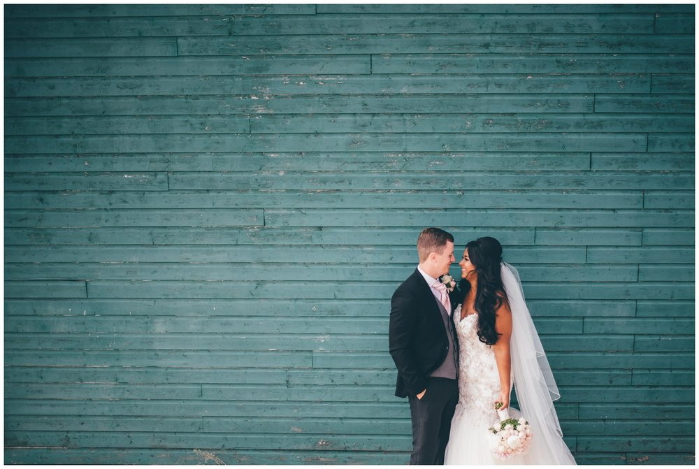 Bride and groom stand against a green wooden backdrop at Aigburth cricket club wedding in Liverpool.
