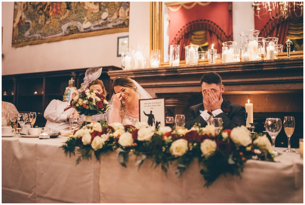 Bride and groom hide their faces as they get embarrassed during the wedding speeches at Peckforton Castle.