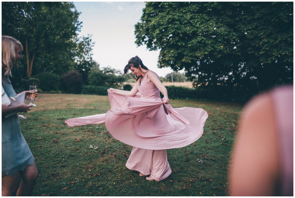 Bridesmaid twirls in her long pink dress at summer wedding at Crabwall Manor in Cheshire.