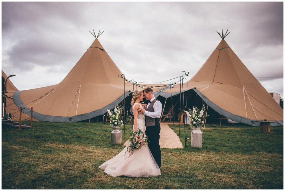 Bride in a blush pink wedding dress with her groom in a tweed suit share a kiss outside their wedding tipi in Staffordshire wedding.