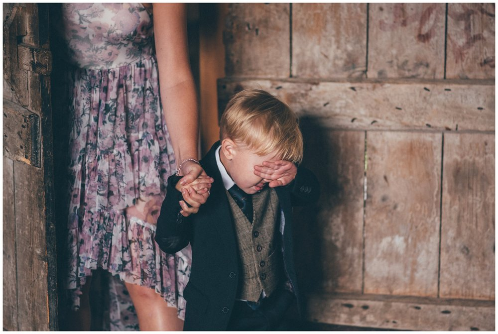 Cute little pageboy hides his face from all the guests shyly at Askham Hall.