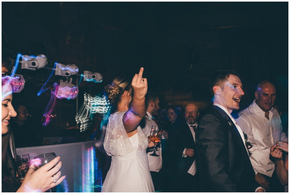 Bridesmaid gives the middle finger after too many photographs on the dance floor at Peckforton Castle.