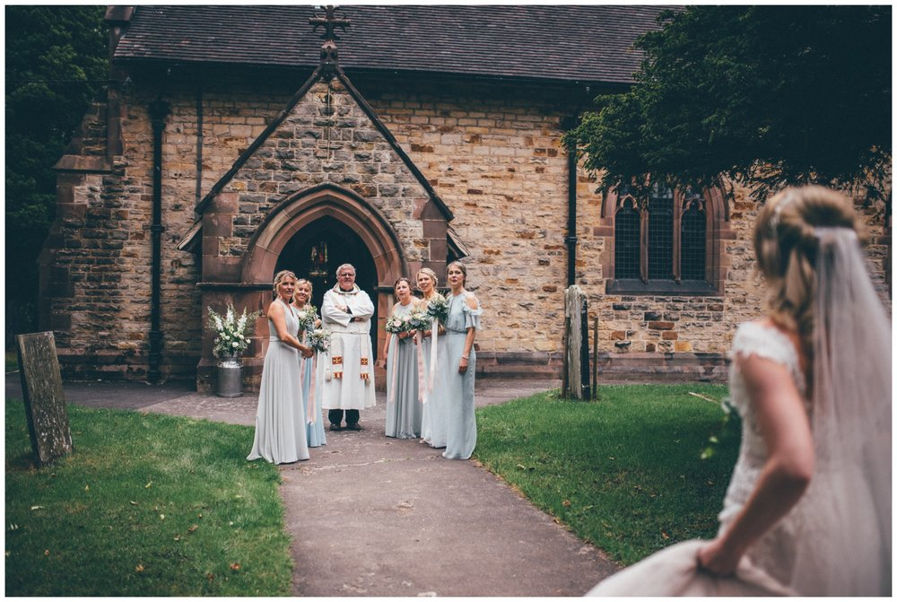 Bridesmaids and vicar await the brides arrival at church.