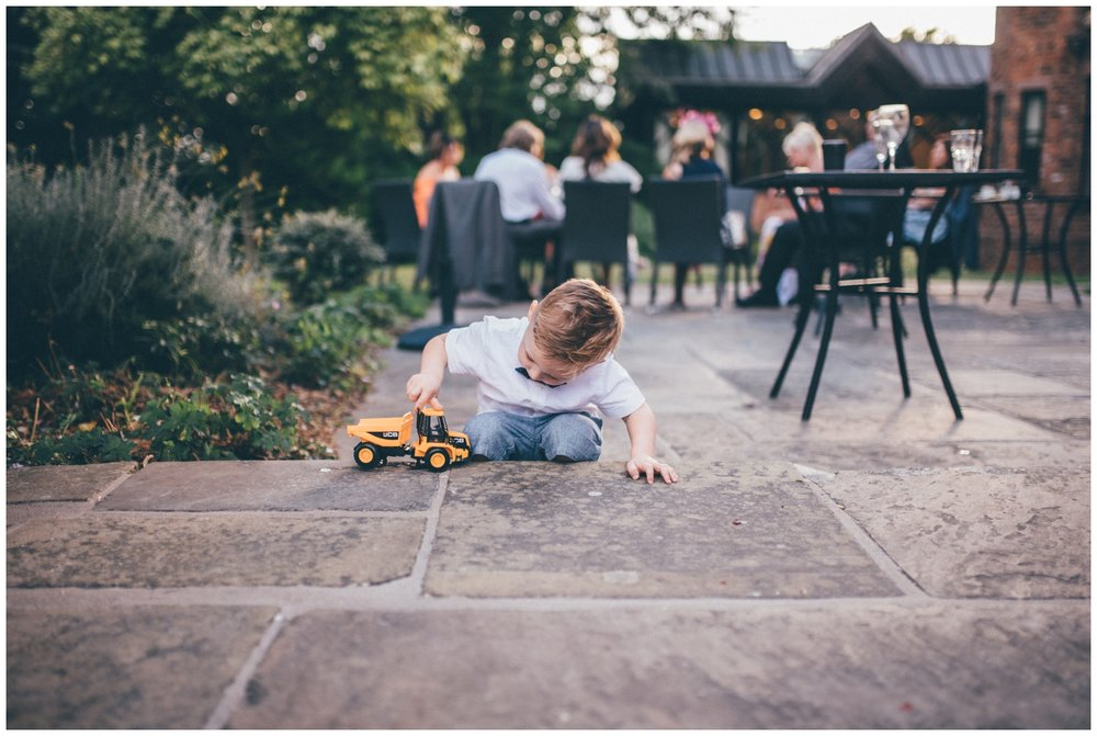 Cute little wedding guest plays with his truck at Crabwall Manor wedding.