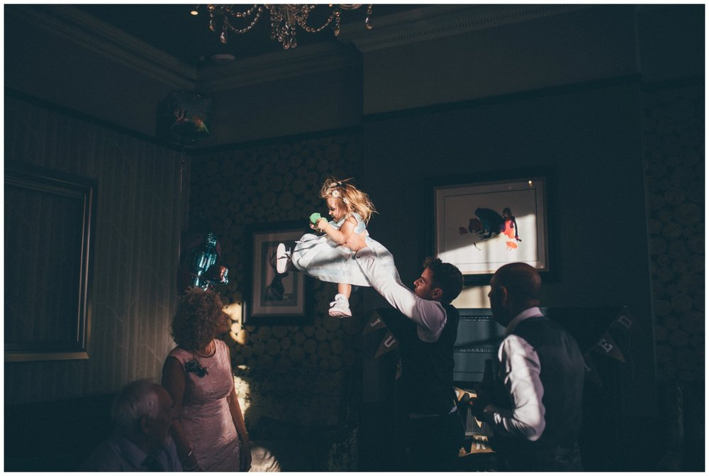 Flowergirl gets thrown in the air by a wedding guest at Oddfellows in Chester.
