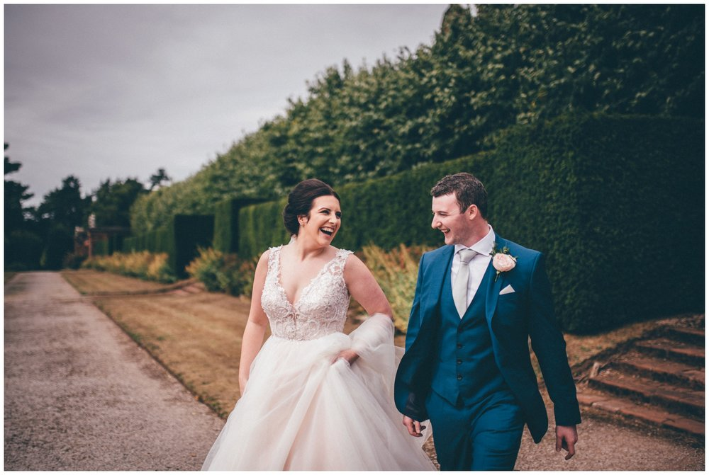 Bride and groom laugh in the gardens at Thornton Manor Cheshire wedding venue.