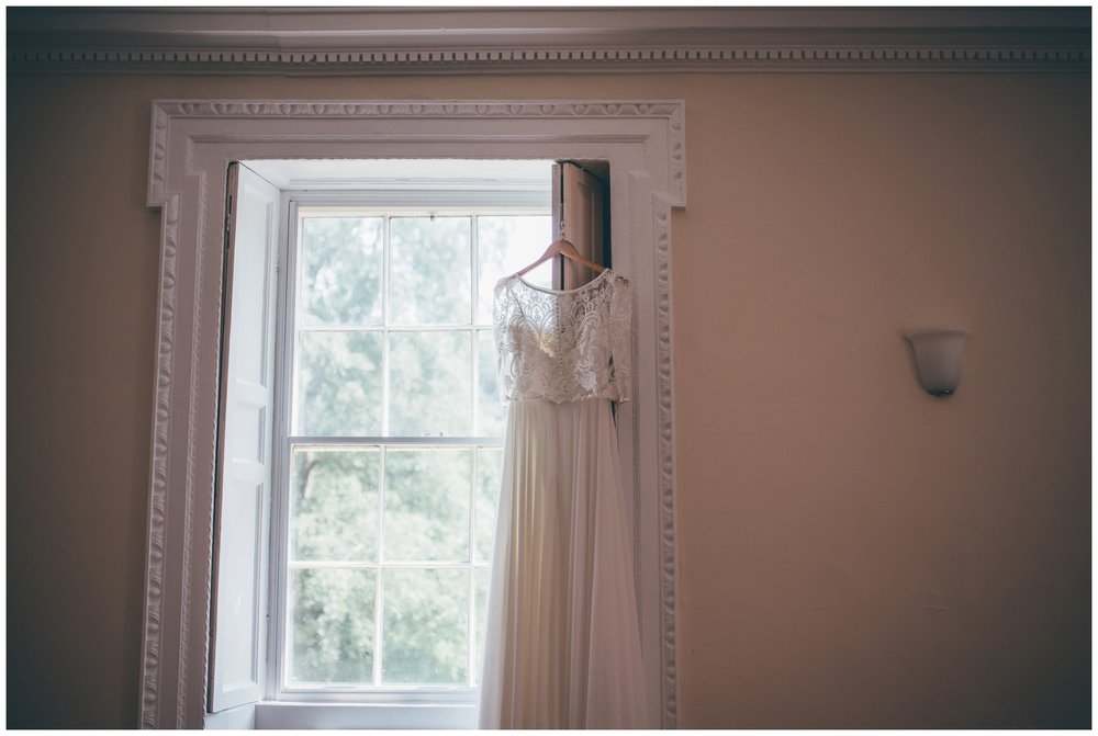 Bride's stunning two-piece wedding gown hung up at Trafford Hall in Cheshire.