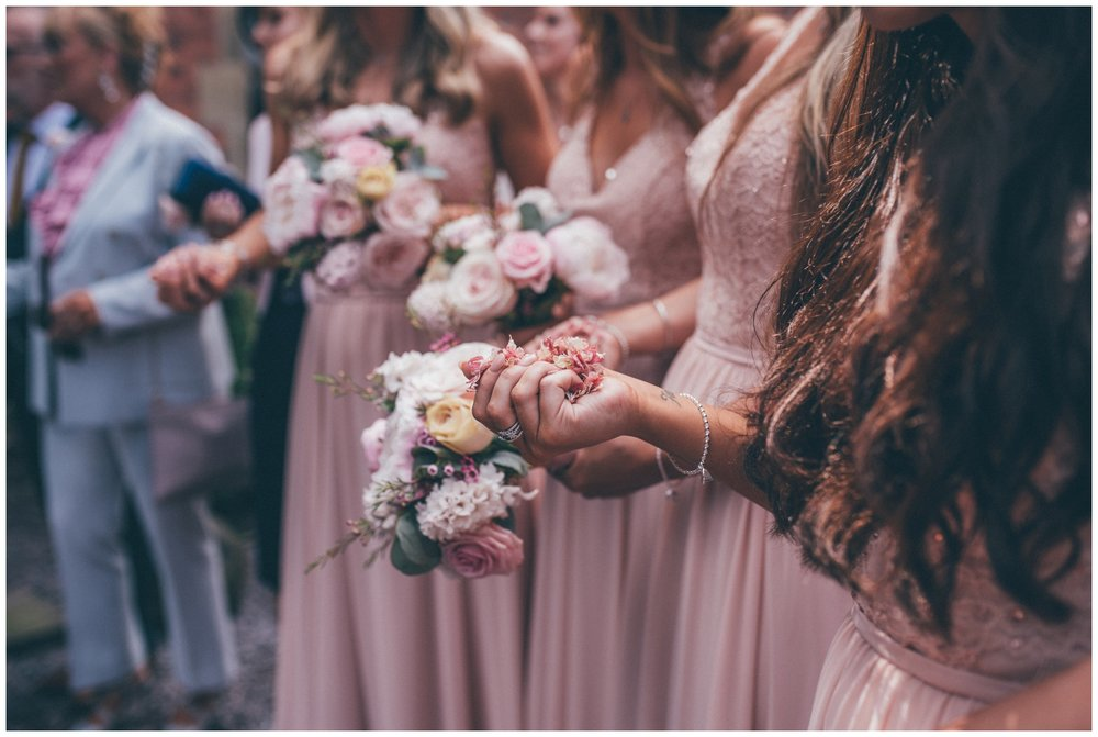 Detail shot of the bridesmaids holding confetti, getting ready to throw it at the bride and groom at new wedding venue, Tyn Dwr Hall in Wales.