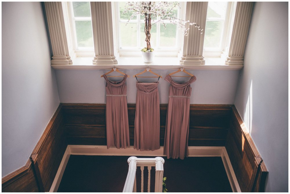 Dusky pink bridesmaids dresses hanging at Trafford Hall in Cheshire.