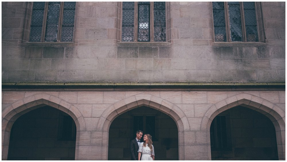 Bride and groom stand together outside gothic old English building in Manchester.